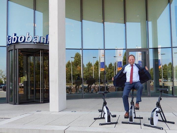Gerben fietst de deskbike bij de Rabobank naar binnen